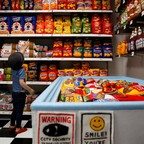 A kid stands among shelves full of chips, cereal, and bread, all made out of felt.