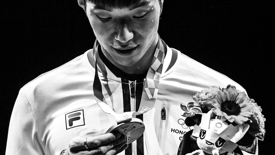 A black and white photo of a man in a track jacket holding a bouquet of flowers and looking down at an Olympic medal while sweat runs down his face
