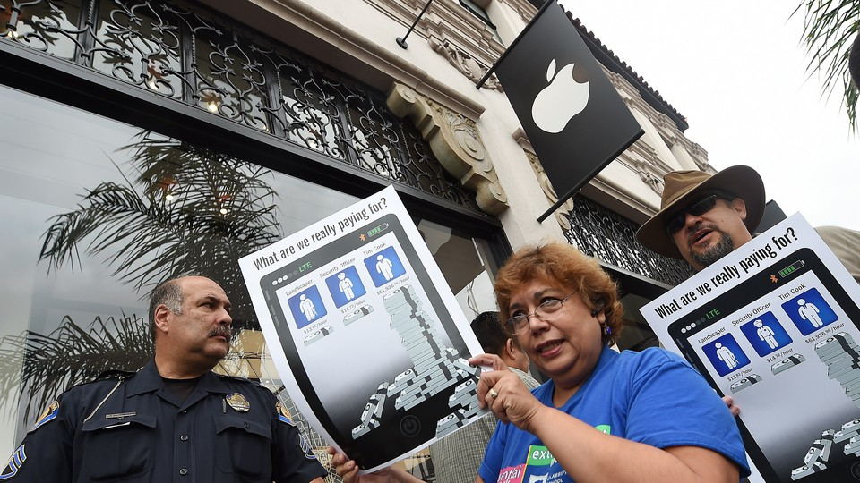 Workers holding signs and protesting in front of an Apple store