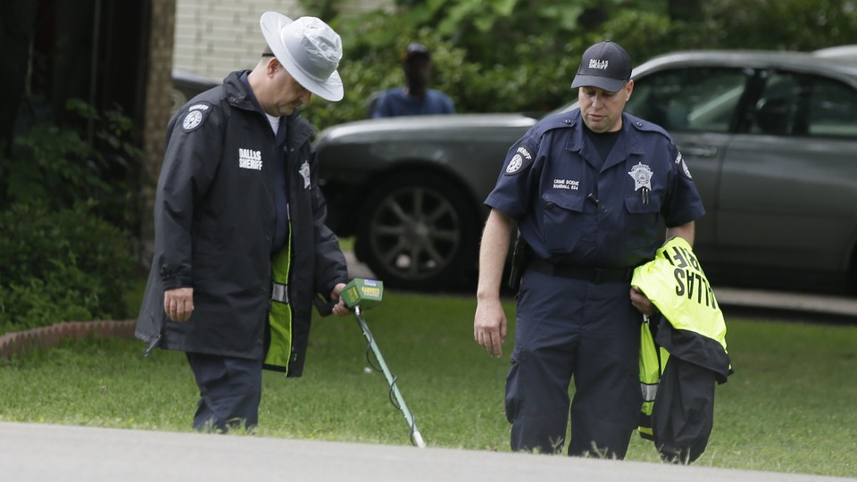 Dallas County Sheriff officials use a metal detector at the intersection near where a police officer killed 15-year-old Jordan Edwards in Balch Springs, Texas, onMay 3, 2017.