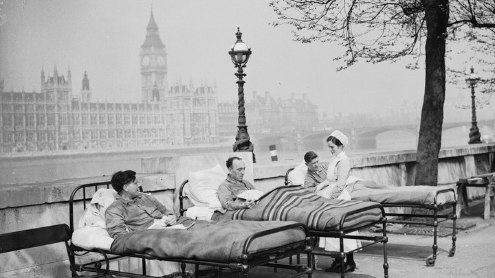 Three men sit in outdoor hospital beds with Westminster Palace in the background.