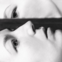 A woman's upturned face half-reflected in a mirror