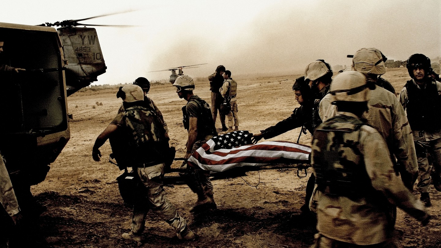 Soldiers on a barren field lift a body on a stretcher, covered in an American flag, into a helicopter.