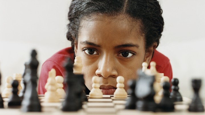 A young girl studies a chess board intently.