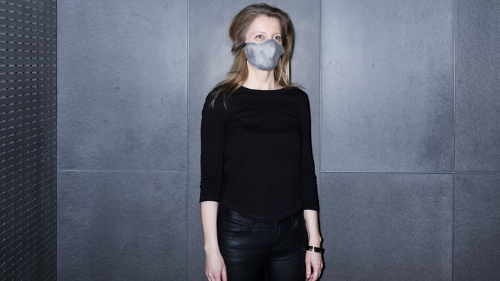 A woman wears a mask made of recycled materials.