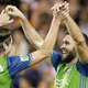 Will Bruin and Gustav Svensson exchange a high-five in their soccer uniforms.