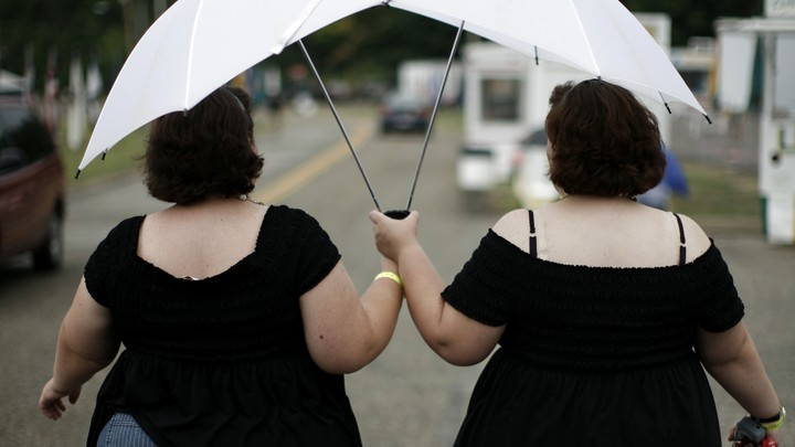 Two women dressed in black dresses holding white umbrellas