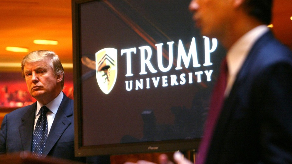 """Donald Trump stands next to a screen that reads """"Trump University."""""""