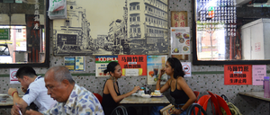 People eat and drink coffee inside a small coffeehouse.