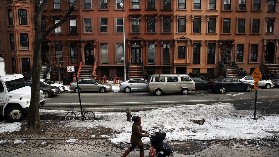 A woman pushes a stroller down a sidewalk lined with brownstones.