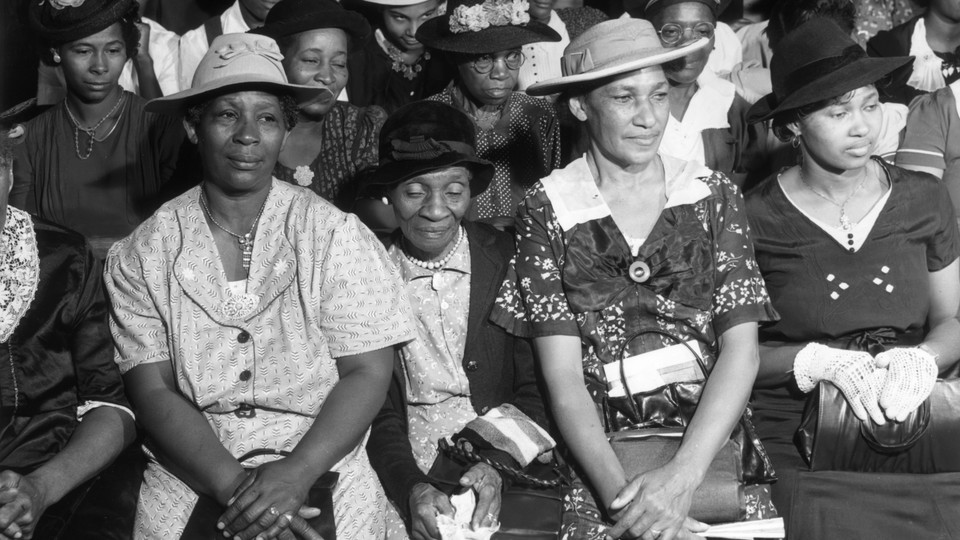 A black-and-white image of Black women sitting in church pews