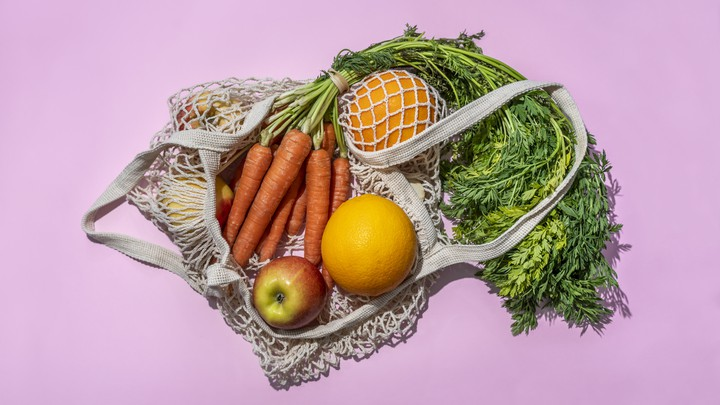 A woven bag containing carrots, apples, two oranges, and some greens, against a lavender background