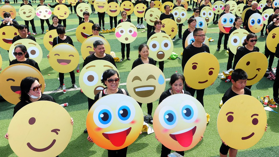 A crowd of people holding up signs with different emoji faces