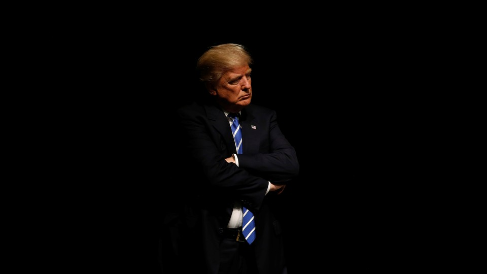 President Trump crossing his arms against a black background
