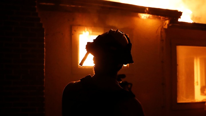 A firefighter monitors a burning structure while battling the Clayton Fire at Lower Lake in California.