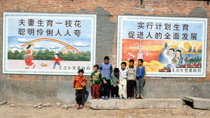 A group of young boys stands close to two large posters extolling the one-child policy.