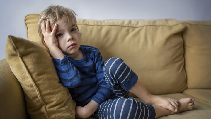 A boy looks bored sitting on a couch
