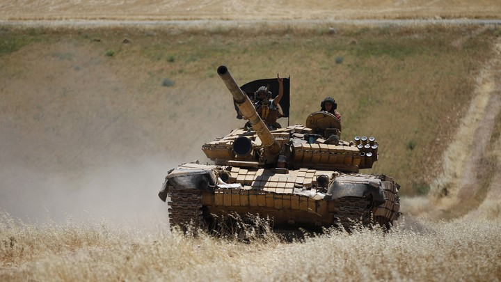 Members of Jabhat al-Nusra drive a tank in Syria.