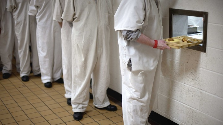 Inmates line up to receive lunch trays through a hole in a cafeteria wall.