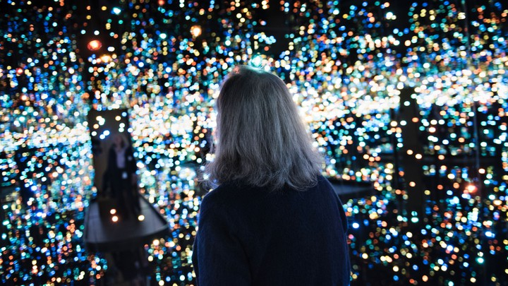 A woman alone in an art installation with hundreds of tiny lights and mirrored walls.