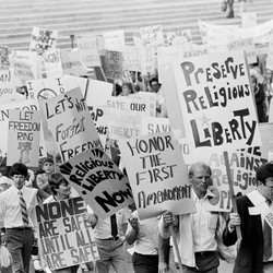 "A black-and-white photo of a Reagan-era protest in front of the Supreme Court's steps, with signs reading ""Preserve religious liberty"" and ""Honor the First Amendment"""
