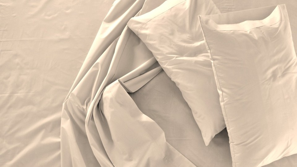 Bunched white bed sheets and two pillows