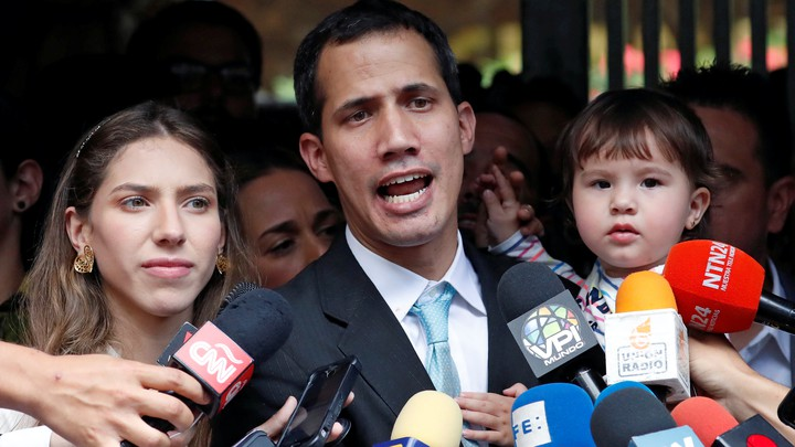 Juan Guaidó talks to members of the press with his wife and daughter outside their home.