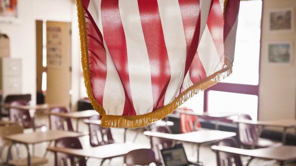 An American flag hangs above a classroom