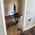 A man stands in an empty room full of mold, shoveling dirt into a wheelbarrow
