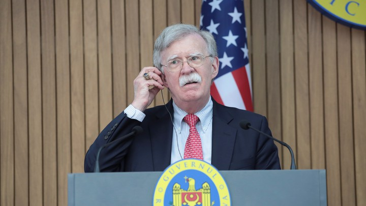 John Bolton stands in front of a podium and an American flag.