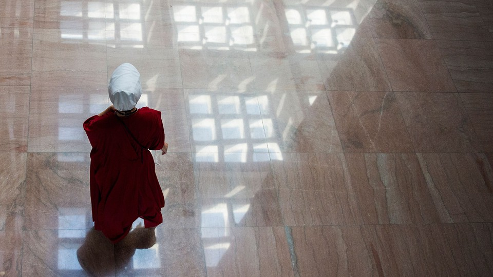 Protester dressed as a Handmaid