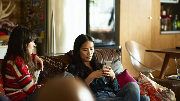 Two women on a sofa; one is holding a phone.