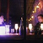 Two women at a bar with a bottle between them.