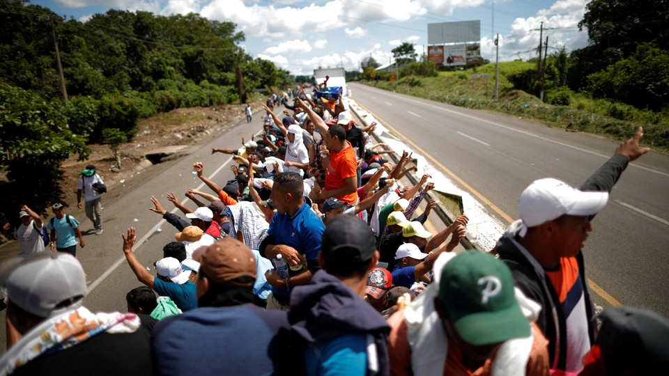Central American migrants hitchhike on a truck along the highway as they continue their journey in Tapachula, Mexico, on October 22, 2018.