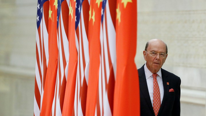 Commerce Secretary Wilbur Ross next to a series of flags