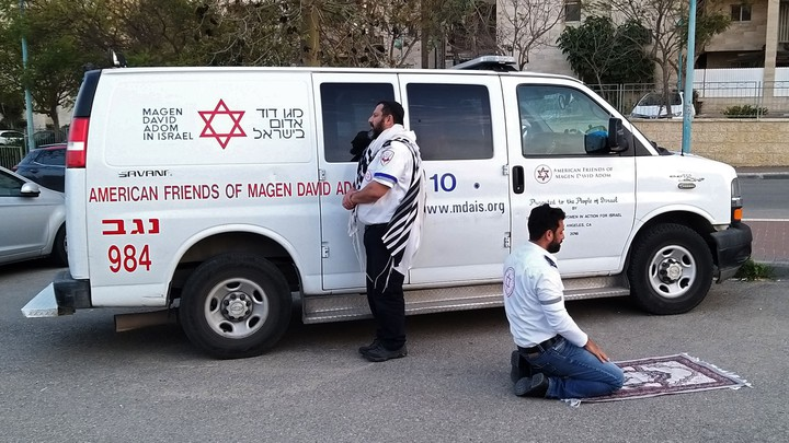 Two medics—one Jewish and one Muslim—praying in Israel.