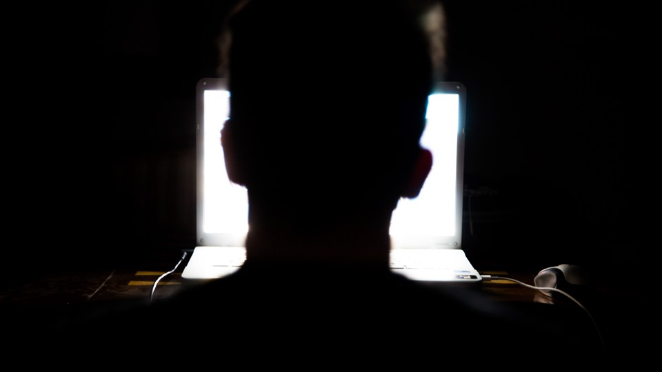 Man sitting in front of a laptop computer in the dark