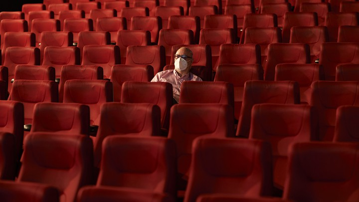 A man wearing a mask sits alone in a theater.