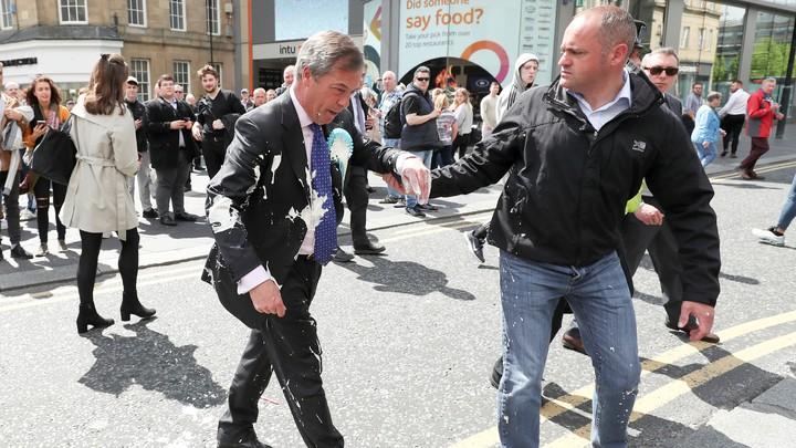 Nigel Farage gestures after being hit with a milkshake.