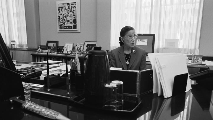 A photograph of Ruth Bader Ginsburg seated at a desk