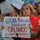 """A woman at a candlelight vigil holds a sign reading """"Aurora families stand with Orlando."""""""
