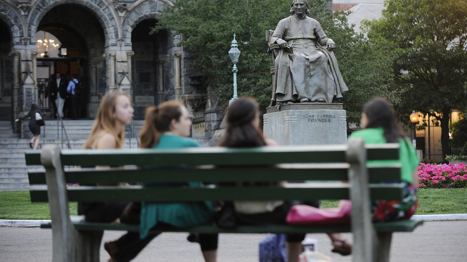 Students sit on a bench in front of a statute of the university founder John Carroll at Georgetown University.
