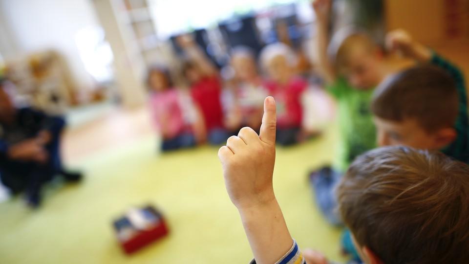 An unrecognizable kindergartener raises his hand