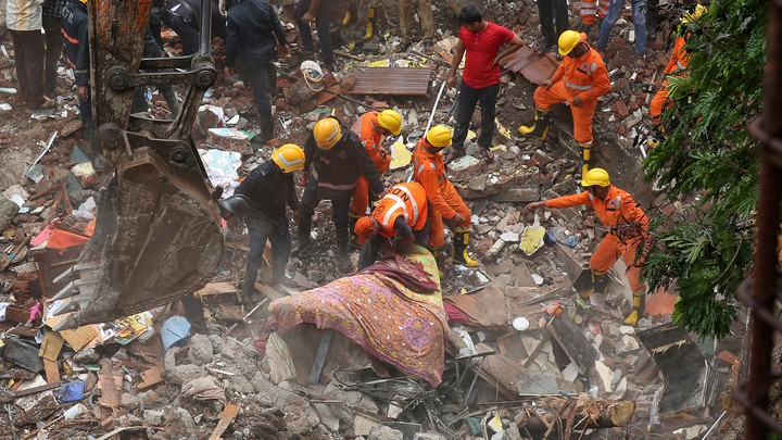 Firefighters and rescue workers search for survivors at the site of the collapsed building on July 25, 2017.