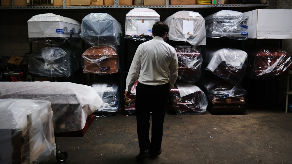 A man standing in front of coffins.