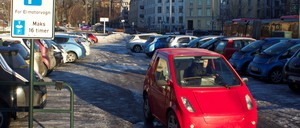 A driver in a small red car leaves a parking lot in Oslo reserved for electric vehicles.