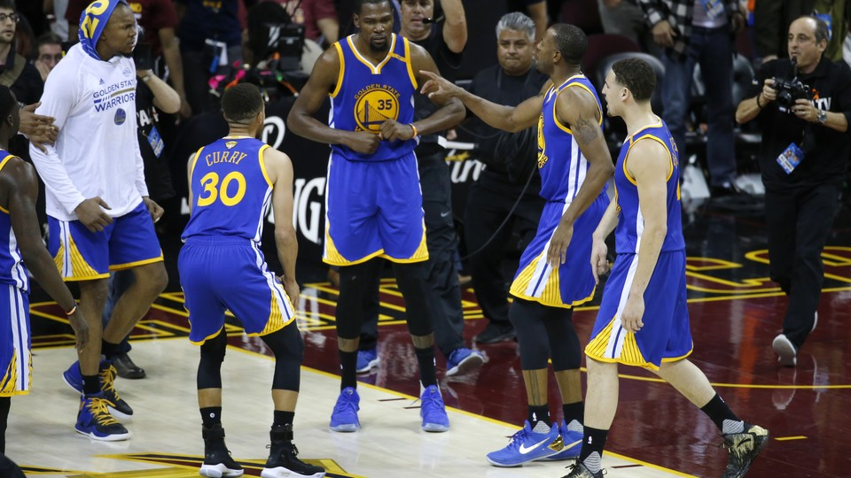 Golden State Warriors forward Kevin Durant celebrates with teammates after the Warriors defeated the Cleveland Cavaliers 118-113 in Game 3 of the NBA Finals in Cleveland, Wednesday, June 7, 2017.