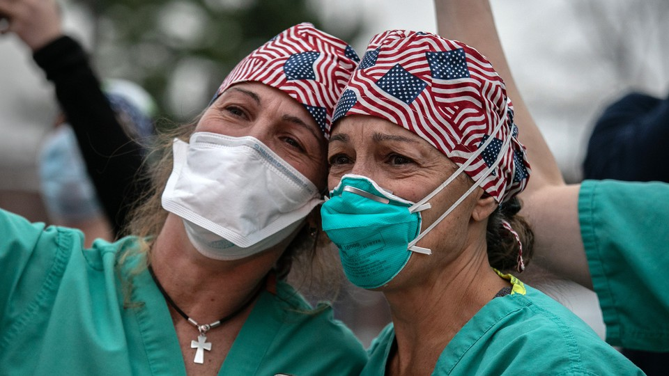 Healthcare workers wearing face masks and bandanas with American flags printed.