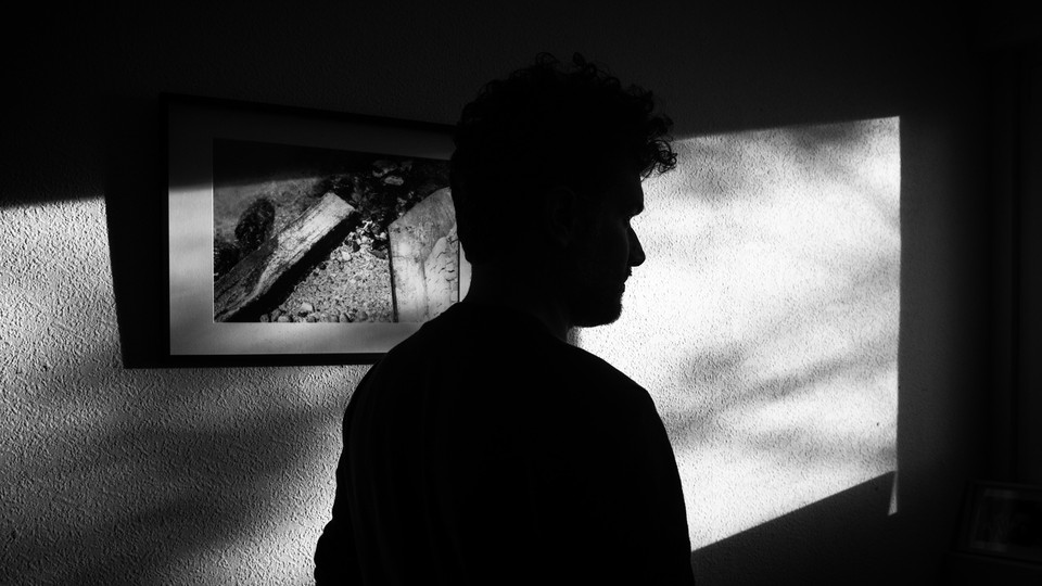 A black-and-white silhouette of a man in a room