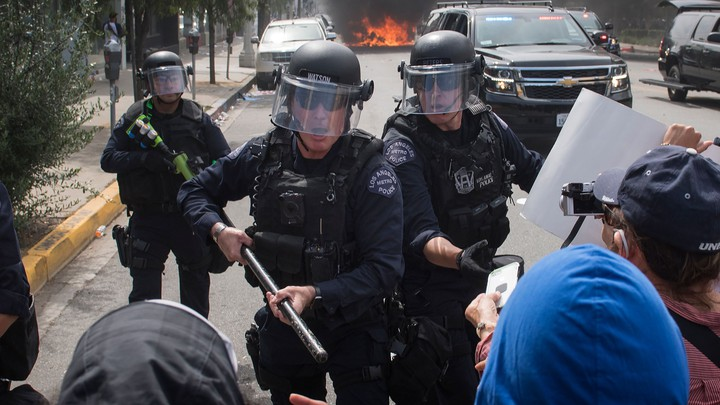 Police officers clash with protesters
